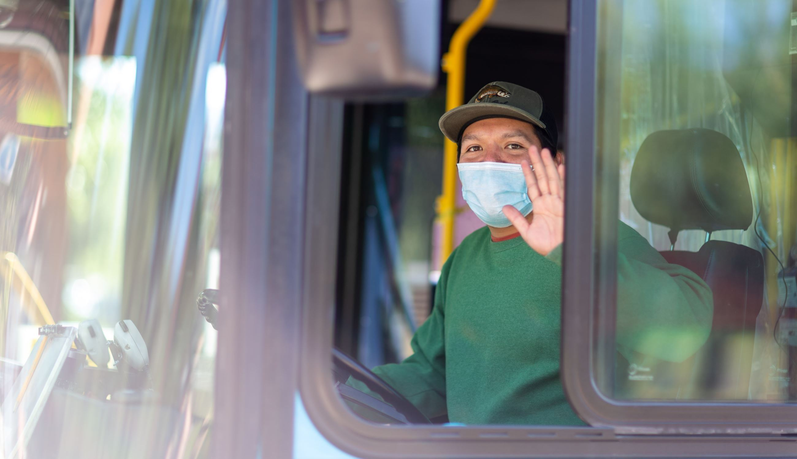 Bus driver smiling and waving in mask