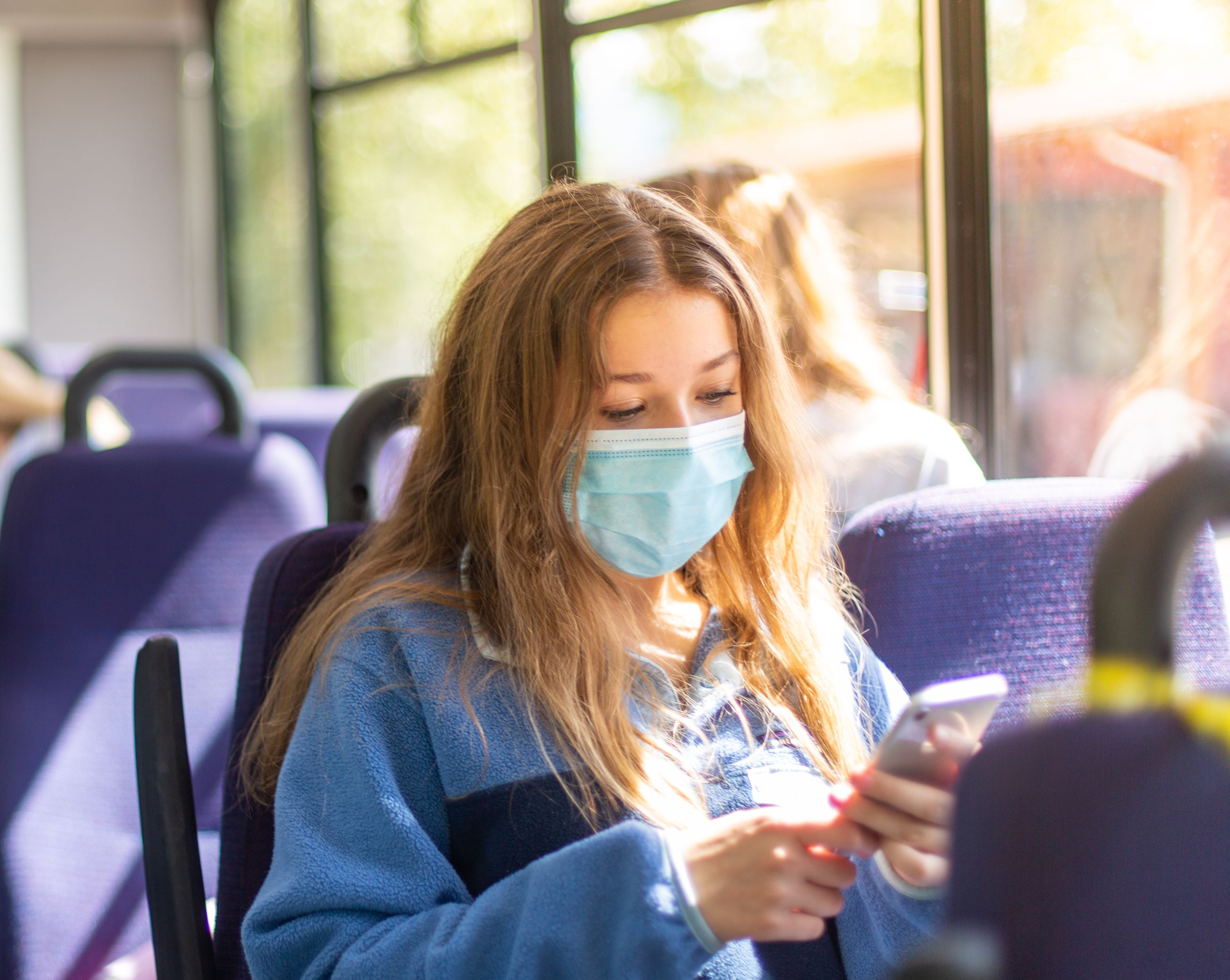 Young girl looking at phone on the bus